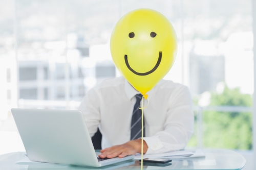 Yellow balloon with happy face hiding businessmans face in bright office